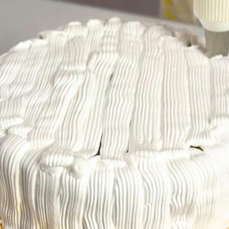 С помощью плоской насадки равномерно наносим крем на торт. После того как торт полностью обмазали кремом, выравниваем его с помощью шпателя.