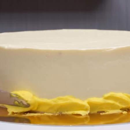 На застывший белый крем по низу торта с помощью мастихина или ножа наносим крем, окрашенный в желтый цвет.