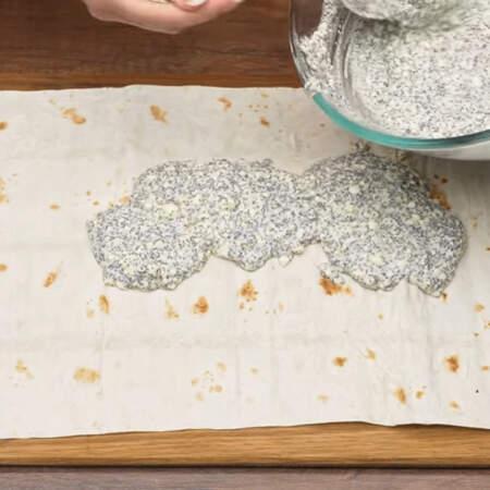 Расстилаем один лист лаваша. На него выкладываем половину творожной массы.
