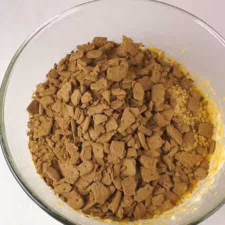 В получившийся крем высыпаем измельченный арахис и шоколадный крекер.