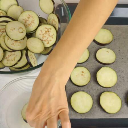 Спустя 20 минут баклажаны обязательно промываем холодной водой. Каждый кружочек баклажана обмакиваем в миску с чесночной водой и кладем на противень.