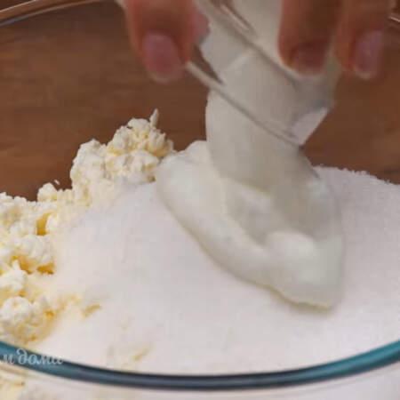 Займемся приготовлением остальной части крема. В миску кладем 500 г творога, насыпаем 300 г сахара и 10 г ванильного сахара. Сюда же добавляем 150 г несладкого йогурта или сметаны.