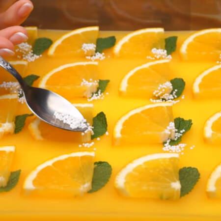 Под каждую дольку апельсина кладем листик свежей мяты. Также для красоты посыпаем сахарными бусинами. Бусинами лучше всего украшать перед подачей, так как они спустя некоторое время могут растаять.