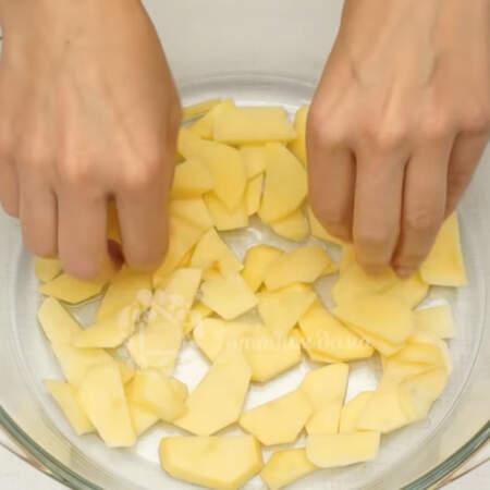На дно формы кладем примерно треть нарезанного картофеля.