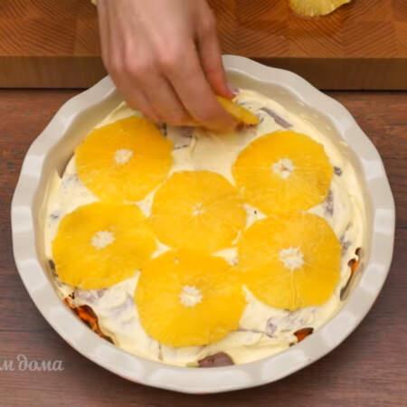 На сметану выкладываем подготовленные кусочки апельсина.