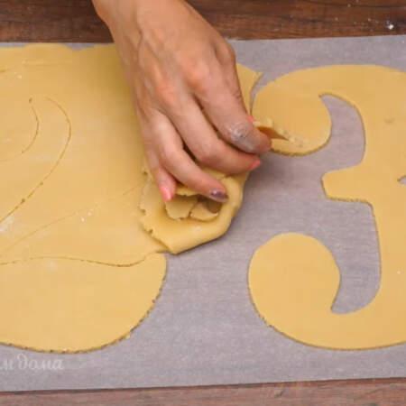 Лишнее тесто убираем и используем по второму разу. Вырезанные цифры вместе с пергаментной бумагой аккуратно перекладываем на противень.