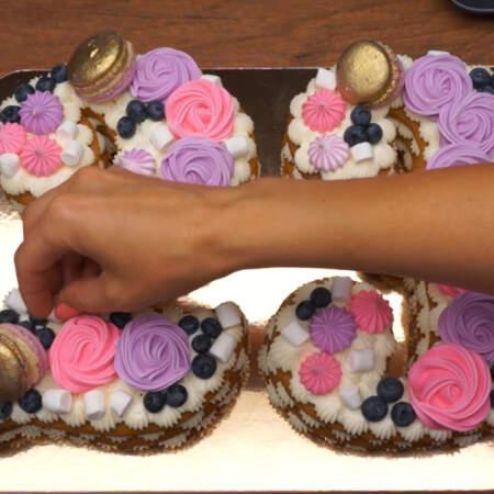 Сверху торт украшаем пирожными макарун, приготовленными безе, свежей голубикой, маленькими маршмеллоу и перламутровыми сахарными бусинами.