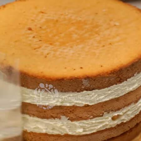 Прошло 6 часов. Предварительно достаем крем, чтобы он успел нагреться до комнатной температуры. Затем достаем торт, вынимаем его из кондитерского кольца, переставляем на подставку и снимаем ацетатную пленку.