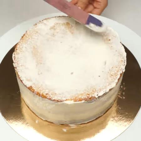 Сначала торт обмазываем небольшим количеством крема, чтобы прибить бисквитные крошки.
