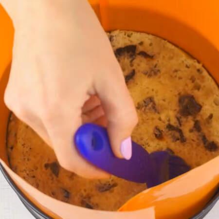 Складываем торт в той же форме что и пеклись коржи. По бокам формы ставим ацетатную пленку или разрезанную пластиковую папку для бумаг, как в моем случае. Первым кладем бисквит с черносливом. Пропитываем его сиропом.