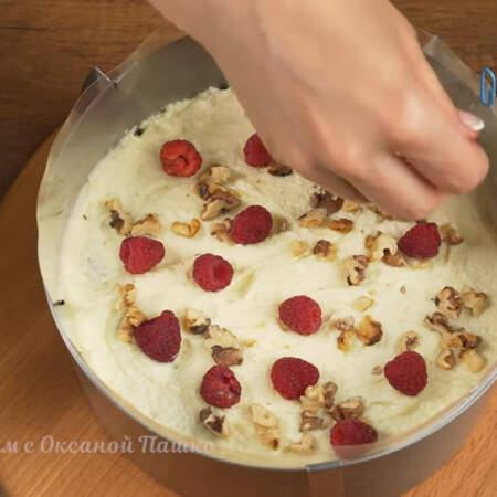 На корж выкладываем крем и распределяем его по всей поверхности. Крем посыпаем подготовленными орехами. Сюда же выкладываем ягоды малины.