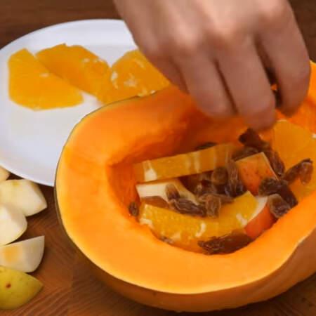 Берем половину уже вымытой и очищенной от семечек тыквы среднего размера. В нее складываем сначала небольшую часть яблок, затем часть подготовленного апельсина и посыпаем изюмом.