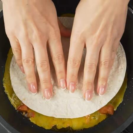 Сразу же, пока яйца еще жидкие, сверху кладем кружок лаваша или тортильи, как в моем случае. Прижимаем его немного к яйцам.