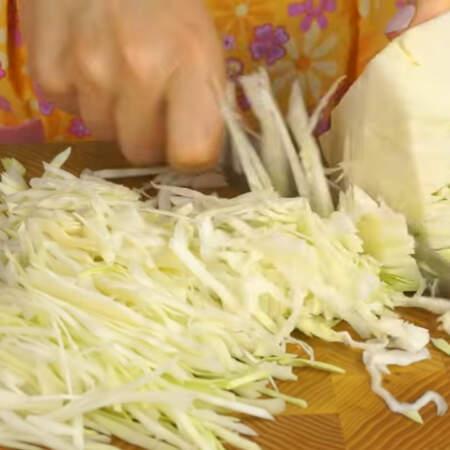 Сначала шинкуем полкилограмма капусты и перекладываем ее в миску.