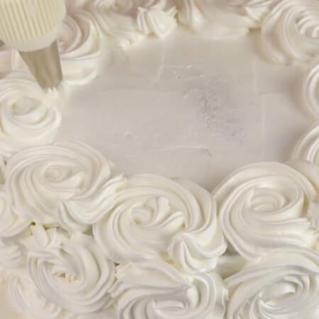 Бока и верх торта украшаем розочками из крема.