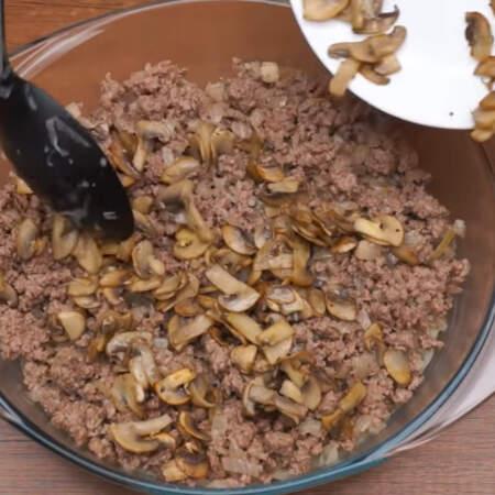 На капусту выкладываем фарш с луком и равномерно распределяем его по форме. Дальше кладем грибы.