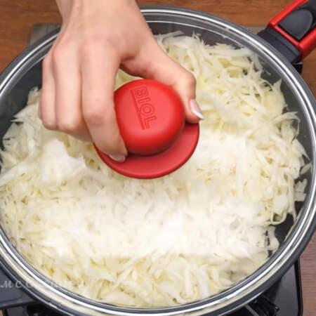 Подготовленную капусту выкладываем на сковороду с небольшим количеством растительного масла. Обжариваем капусту примерно 3 минуты на большом огне, перемешивая лопаткой, а затем сковороду накрываем крышкой и убавляем огонь до минимума.