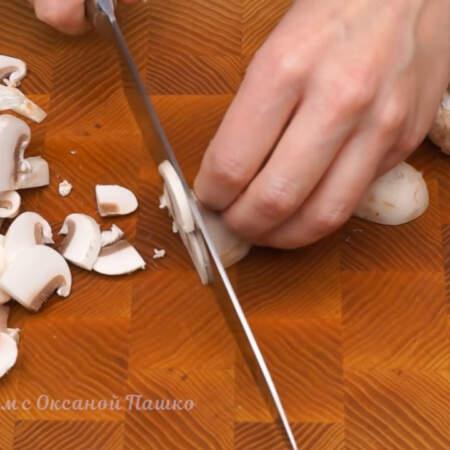 Пока тушится капуста, подготовим остальные ингредиенты. 300 г шампиньонов разрезаем пополам и нарезаем пластинками.